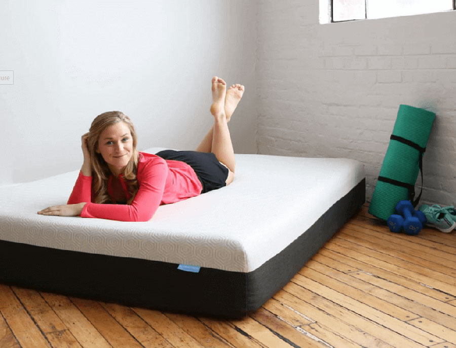 Puffy Mattress vs Puffy Lux Reviews - Girl laying on stomach on mattress with no sheets.
