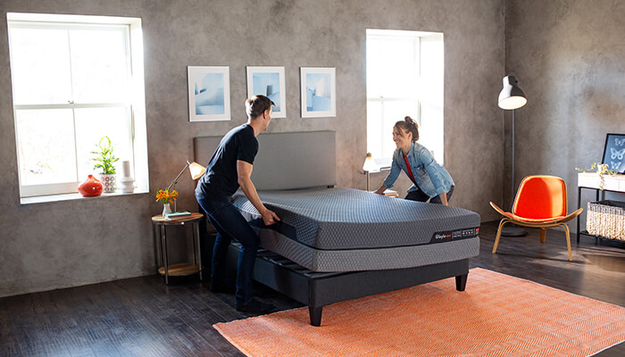 Girl and guy standing on either side of bare mattress. Looks like they are getting ready to turn it over.