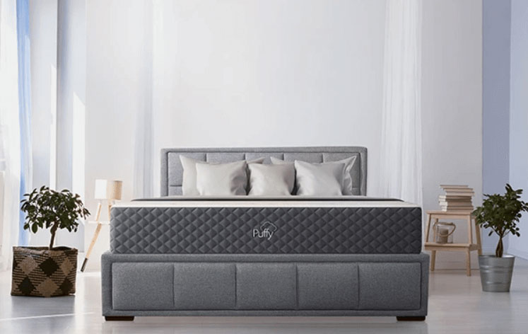 Puffy mattress in bedroom setting with headboard.